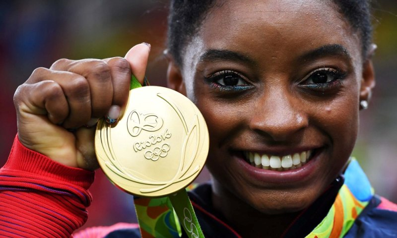 RIO DE JANEIRO, BRAZIL - AUGUST 09: Simone Biles of the United States poses for photographs with her gold medal after the medal ceremony for the Artistic Gymnastics Women's Team on Day 4 of the Rio 2016 Olympic Games at the Rio Olympic Arena on August 9, 2016 in Rio de Janeiro, Brazil. (Photo by Laurence Griffiths/Getty Images) ORG XMIT: 631390975 ORIG FILE ID: 587771206